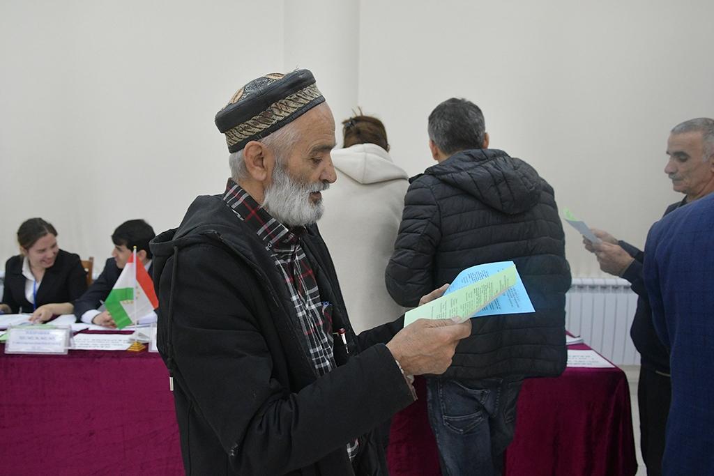 Ein Mann mit tradtioneller Kopfbedeckung im Wahllokal
