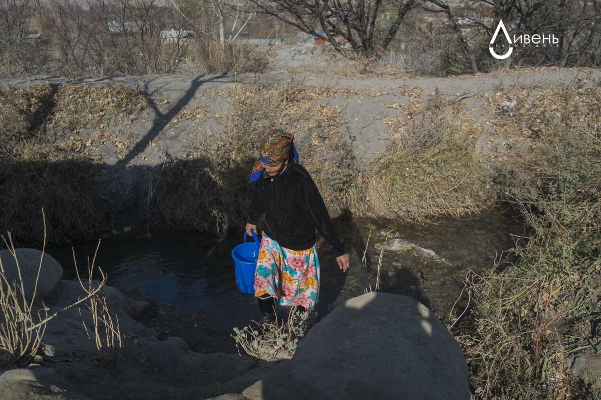 Salamat, vivant dans la partie kirghize du village, collecte l'eau dans l'aryk qui approvisionne l'ensemble du village