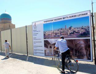 Un homme à vélo contemple le projet de centre commercial dans le centre historique de Boukhara