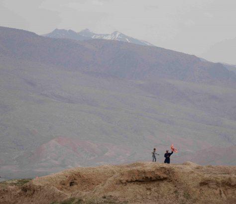 Des cerfs-volants traversent le ciel des abords de Pendjikent, devant un impressionnant paysage de montagnes